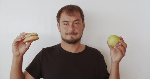 Man choosing healthy or unhealthy food. Man making a choice between apple and Footage
