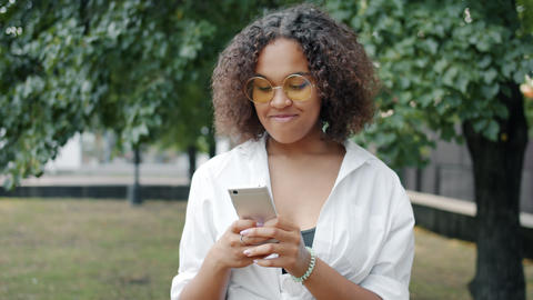 Afro-American woman enjoying communication with smartphone outdoors in park Footage