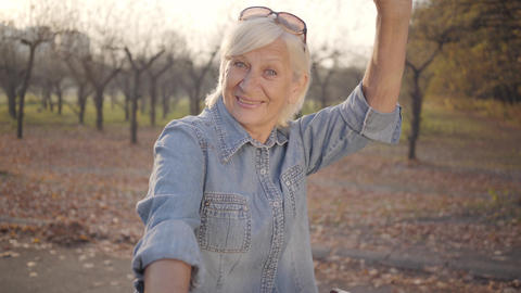 Close-up portrait of joyful mature Caucasian lady in denim standing with bicycle Footage