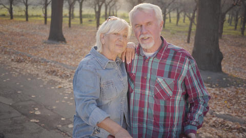 Smiling senior Caucasian couple standing in sunlight outdoors and talking Footage