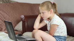 Young girl is watching movie on her laptop computer Footage