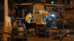 Man enjoys music on mobile in street stall,Surabaya,Java,Indonesia Footage