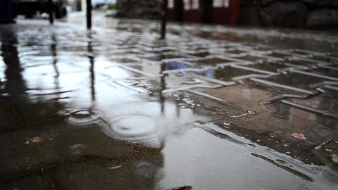 Splashes of water falling in puddles formed on a driveway slabs situated near a Footage