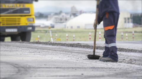 Road construction worker leveling asphalt using rake Footage