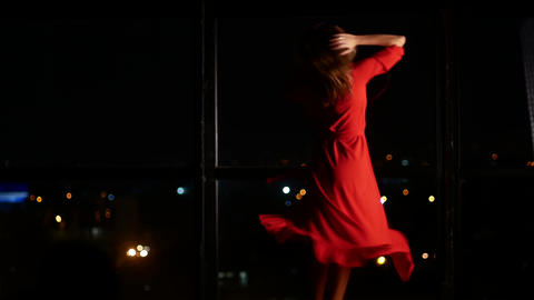 A girl in a red elegant dress is dancing against the backdrop of a large window Live Action
