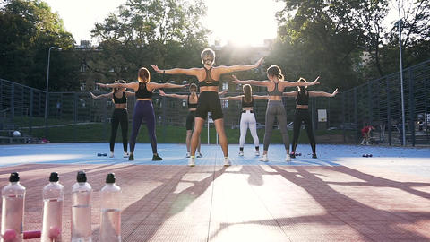Seven unknown athletic women standing on the sportground and doing fitness Footage