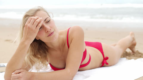 Sexy woman in a bikini relaxes on a sandy beach at the ocean Footage