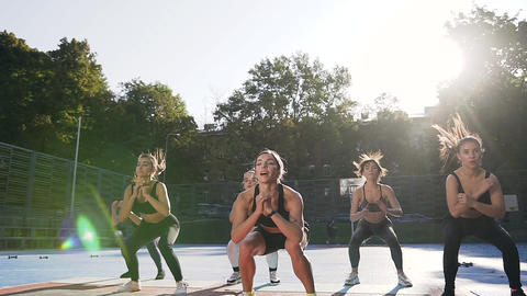 Fitness team of good-looking slim sporty women doing jumping squats on their Live Action