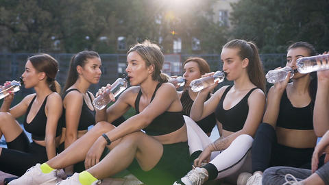 Likable slender sporty fitness women sitting on the outdoor stadium's floor and Footage