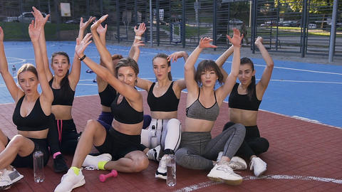 Fitness female team sitting on the outdoor stadium's floor and waving their Footage