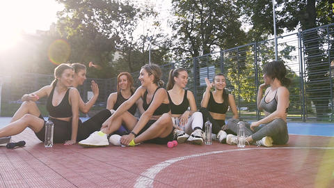 Smiling happy sporty slim women resting after fitness lesson and giving each Live Action