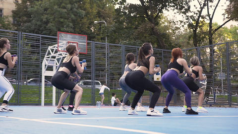 Back view of group of attractive young sporty girls which doing squat exercises Footage