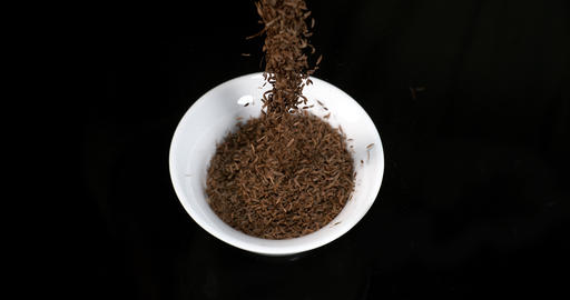 Caraway or Cumin Seeds, carum carvi, Seeds falling into a Bowl against Black Background, Slow motion Live Action