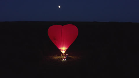 Aerial view red air balloon in heart shape preparing to flight on field at night. Red hot aerostat Footage