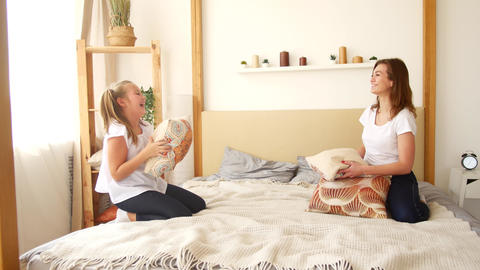 Mom and daughter throw pillows while sitting on the bed. Having fun and fooling Footage