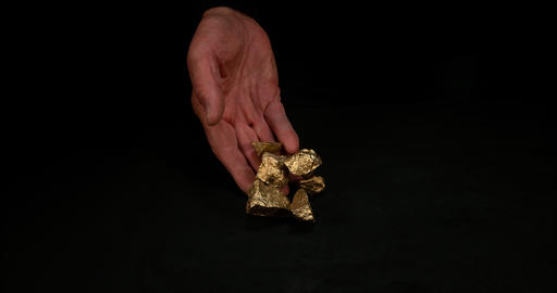 Hand and Gold Nuggets, Nugget, Falling on Black Background, Slow Motion 4K Footage