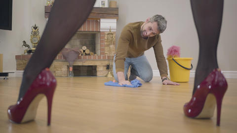 Joyful Caucasian husband or henpecked washing the floor on the knees and Footage