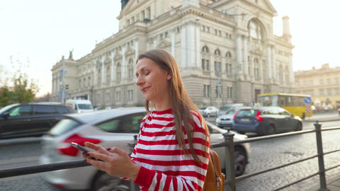 Young woman walking down an old street using smartphone at sunset. Communication Footage