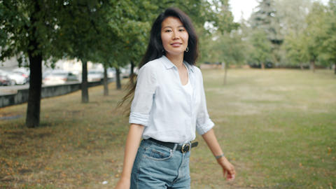Slow motion of slender Asian lady walking outdoors in green park then turning Footage