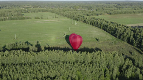 Aerial view air balloon in heart shape on green field, forest background. Hot air balloon preparing Footage