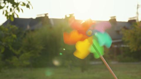 Plastic rainbow windmill rotates against the setting sun ビデオ