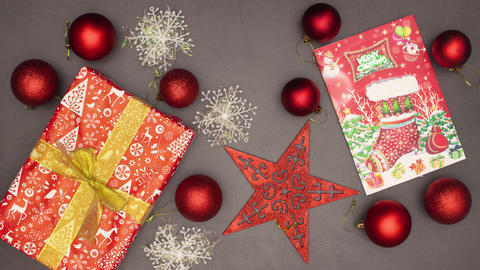 Christmas red decoration with balls, card and presents appear on grey background - Stop motion Animation