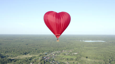 Heart love air balloon flying over green field and forest on skyline view. Aerial view aerostat in Footage