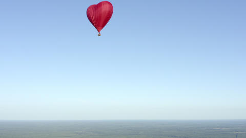 Red air balloon in love heart shape flying in blue sky over green field aerial view. Hot aerostat Footage
