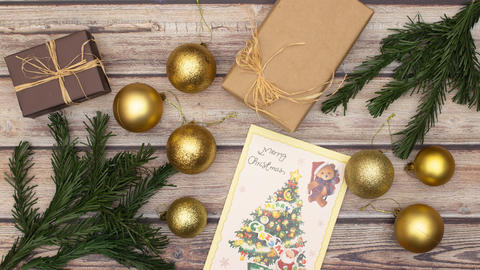 Beautiful Christmas golden decoration, presents, garland, card, balls appear on the table - Stop Animation