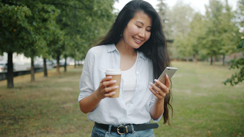Young Asian lady walking in park using smartphone holding take out coffee Footage