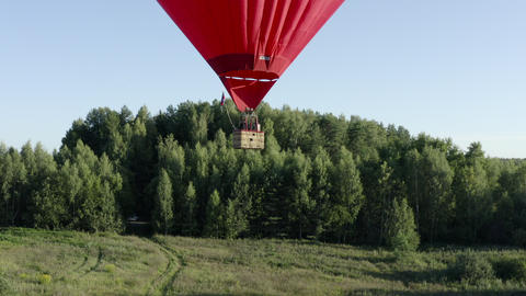 Hot air balloon in heart shape flying over green field and summer forest. Aerostat with basket Footage