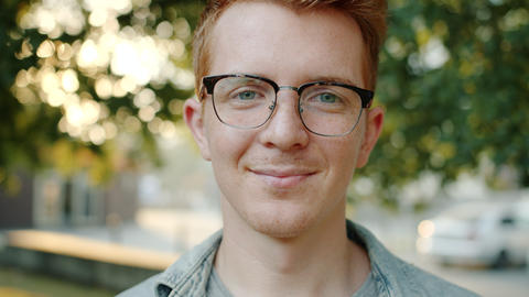 Close up slow motion of attractive student in glasses smiling outdoors in park Footage