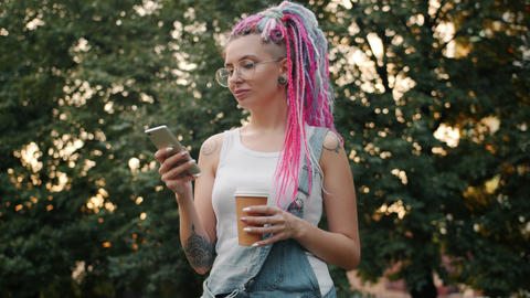 Pretty student with colored hair using smartphone holding coffee outdoors Footage