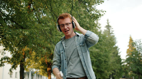 Slow motion of guy in headphones dancing singing outdoors holding smartphone Footage