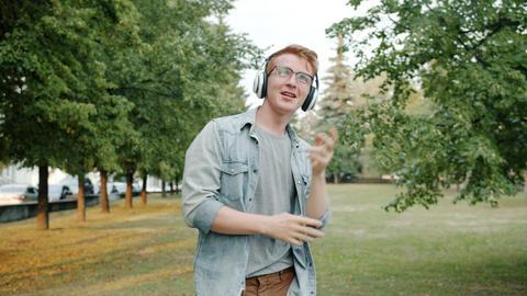Cheerful student dancing outdoors in city park wearing headphones having fun Footage