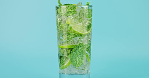 Cold sparkling mojito cocktail in a glass against blue background, close-up slow Live Action