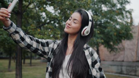 Asian girl wearing headphones taking selfie with smartphone camera outdoors Footage