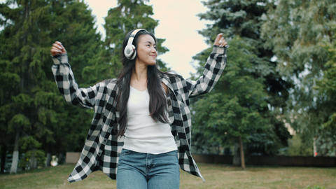 Happy Asian student dancing outdoors wearing wireless headphones smiling Live Action