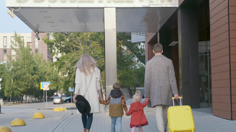 Family travelers walk down the street to the hotel Live Action