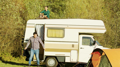 Young girl relaxing on top of retro camper van in mountain wilderness Footage