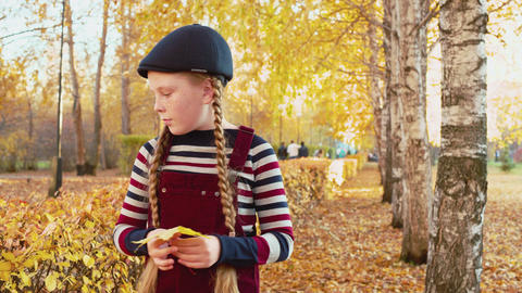 Cute pensive child holding yellow maple leaf in park Live Action