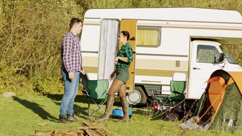 Boyfriend spinning around her girlfriend in front of their retro camper van Footage