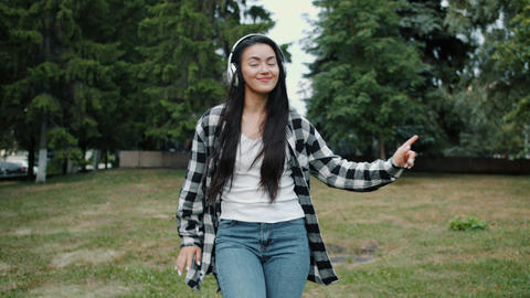Slow motion of young Asian lady in headphones dancing in urban park alone Footage
