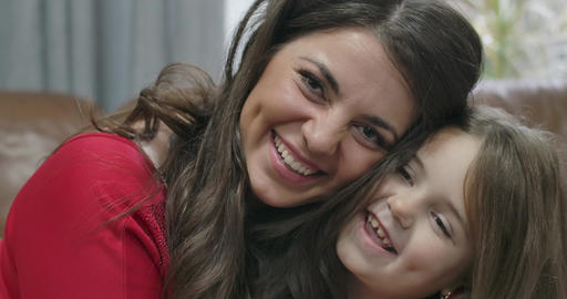 Close-up of brunette Caucasian woman and little girl rubbing noses, looking at Live Action