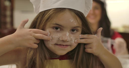 Close-up portrait of joyful Caucasian girl drawing lines on face with flour. Her Footage