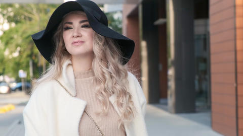 Close-up of a happy charming lady in a hat and coat walks the street Footage