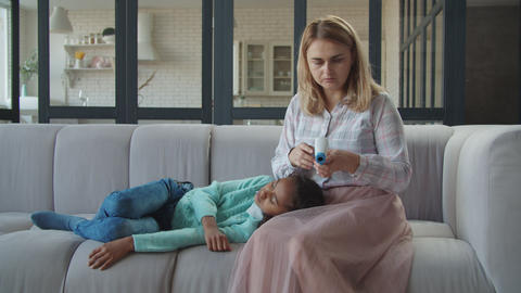Mom measuring temperature of sick girl with thermometer Live Action