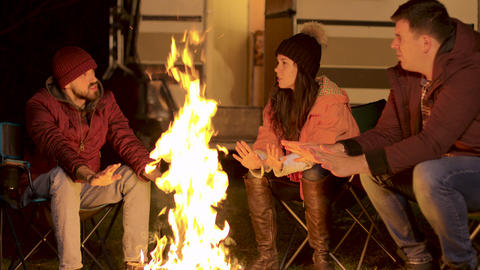 Handheld footage of friends warming their hand on camp fire in a cold autumn Live Action