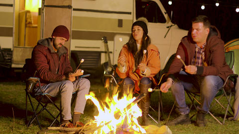 Friends relaxing around camp fire and roasting marshmallows on sticks Footage