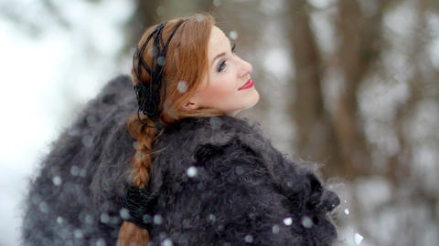Beautiful girl in a down scarf under a winter snowfall in the forest Footage